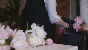 美丽的女孩卖花人做花卉构成并且微笑 花事务 做美丽的花束的女性卖花人在 影视素材