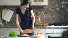 美丽的女孩厨师薄饼,当谈话在手机和在家时微笑在厨房里 影视素材