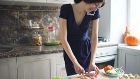 美丽的女孩厨师薄饼,当谈话在手机和在家时微笑在厨房里 股票视频