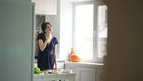 美丽的女孩厨师,当谈话在手机和在家时微笑在厨房里 股票视频