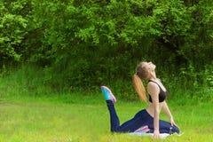 美丽的女孩参与体育,瑜伽,在海滩的健身由河在一个晴朗的夏日 免版税库存图片