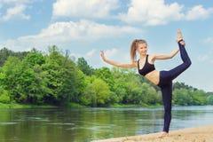 美丽的女孩参与体育,瑜伽,在海滩的健身由河在一个晴朗的夏日 免版税图库摄影