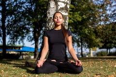 美丽的女孩参与单独实践瑜伽在公园 免版税库存照片