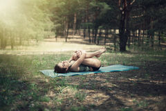 美丽的女孩参与瑜伽在森林里 免版税库存图片