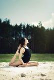美丽的女孩参与瑜伽在沙子的森林里 库存图片