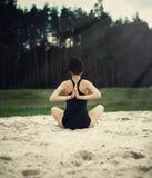 美丽的女孩参与瑜伽在沙子的森林里 免版税库存图片
