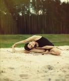 美丽的女孩参与瑜伽在沙子的森林里 免版税库存照片