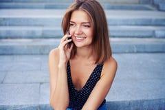 美丽的女孩发表演讲关于手机与开朗的笑 库存照片