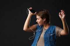美丽的女孩听到与她的电话的音乐在黑背景 免版税库存图片