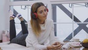 美丽的女孩听在放置在格子花呢披肩的耳机的音乐在窗口附近 影视素材