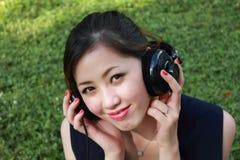 美丽的女孩听的音乐公园 免版税图库摄影