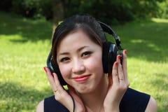美丽的女孩听的音乐公园 免版税库存图片