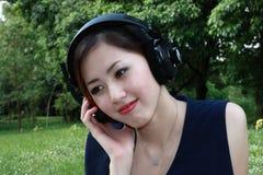 美丽的女孩听的音乐公园 免版税库存照片