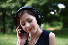美丽的女孩听的音乐公园 库存照片