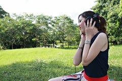 美丽的女孩听的音乐公园 库存图片