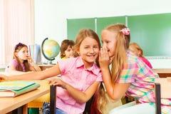 美丽的女孩告诉秘密对其他在学校 库存图片