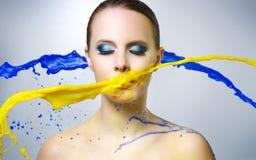 美丽的女孩和五颜六色的油漆飞溅 免版税图库摄影