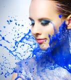 美丽的女孩和蓝色油漆飞溅 库存图片