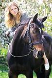 美丽的女孩和马在春天庭院里 免版税图库摄影