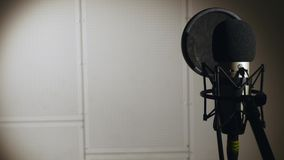 美丽的女孩唱年轻人 唱歌入话筒的年轻歌手 画象接近歌手 录音室 库存图片
