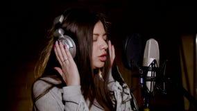 美丽的女孩唱年轻人 唱歌入话筒的年轻歌手 画象接近歌手 录音室 免版税库存图片