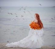 美丽的女孩喜欢在海滩的一只天鹅 库存照片