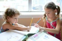 美丽的女孩回家家庭作业一点 免版税图库摄影