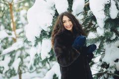 美丽的女孩在一个多雪的森林里 免版税库存图片