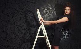 美丽的女孩在一个白色楼梯站立 免版税库存照片