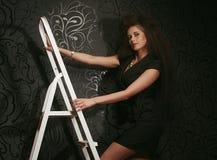美丽的女孩在一个白色楼梯站立 库存图片