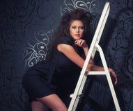美丽的女孩在一个白色楼梯站立 免版税库存图片