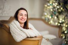 美丽的女孩在一个软的格子花呢披肩等待的圣诞节假日 在背景的Xmas树 免版税库存照片