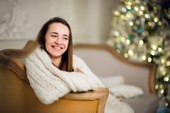 美丽的女孩在一个软的格子花呢披肩等待的圣诞节假日 在背景的Xmas树 免版税图库摄影