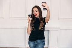 美丽的女孩在一个轻的演播室在电话喝咖啡并且做selfie 与卷发和红色的一个美妙的模型 图库摄影