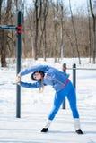 美丽的女孩在一个运动场再舒展在冬天 免版税库存照片