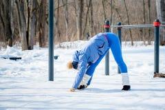 美丽的女孩在一个运动场再舒展在冬天 库存照片