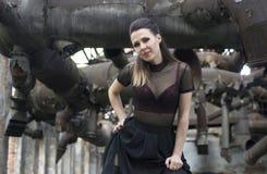 美丽的女孩在一家被放弃的工厂 库存照片