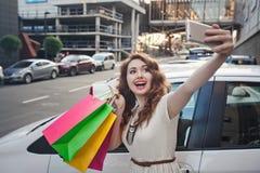 美丽的女孩在一辆白色汽车附近站立,做购物, selfie 库存图片