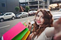 美丽的女孩在一辆白色汽车附近站立,做购物, selfie 库存照片