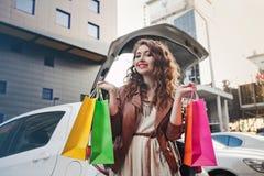 美丽的女孩在一辆白色汽车附近站立,做购物 库存照片