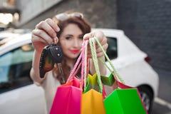 美丽的女孩在一辆白色汽车附近站立,做购物 免版税库存照片