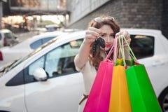 美丽的女孩在一辆白色汽车附近站立,做购物 图库摄影