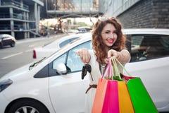 美丽的女孩在一辆白色汽车附近站立,做购物 免版税库存图片