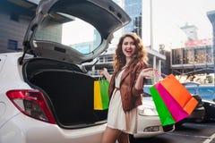 美丽的女孩在一辆白色汽车附近站立,做购物 免版税图库摄影