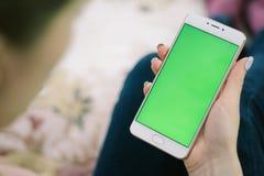 美丽的女孩在一绿色scre的手上的拿着一个智能手机 免版税库存照片