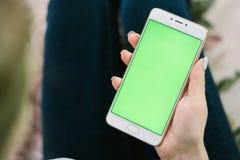 美丽的女孩在一绿色scre的手上的拿着一个智能手机 免版税库存图片