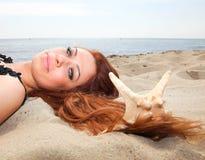 美丽的女孩在与壳自然假期的沿海说谎 免版税库存照片