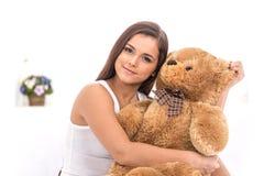 美丽的女孩在与玩具熊的床上 免版税库存图片