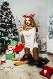 美丽的女孩在与礼物的一棵圣诞树附近坐 库存图片