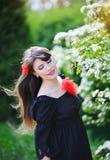 美丽的女孩在公园在春天有一朵红色花的 库存图片